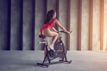Young healthy woman in red sportswear rides on the exercise bike. Sport and healthy lifestyle concept