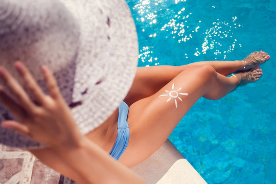 Woman with sun protection cream in the shape of sun on her leg. People, summer, holiday and healthcare concept