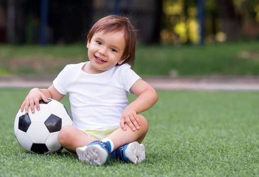 Little toddler boy sitting with legs crossed on football field in summer day with soccer ball. Happy child playing football outdoors. Active childhood concept