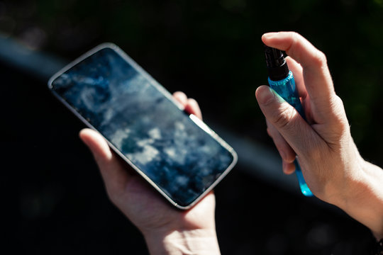 Young person cleaning a mobile phone display by spraying washing solution on it outdoor – Woman holding a smartphone while removing dirt from the surface of the screen