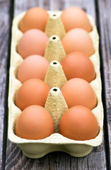 Fresh eggs on a wooden table with copy space, vertical