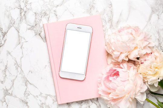 Mobile phone with a white and pink notebook and piony flowers on a marble background