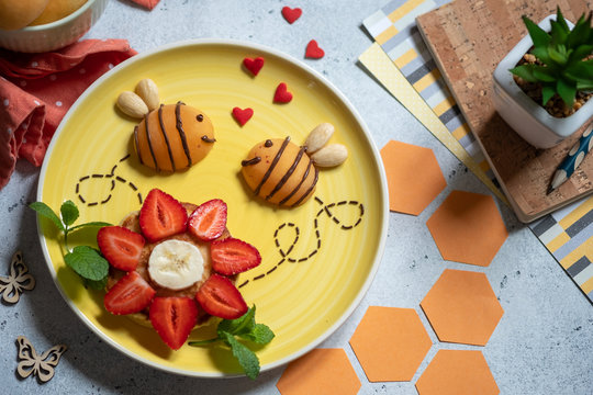 Pancake with fruits look like a flower and bees for kids breakfast