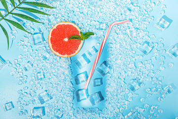 cold drink. ice on a light blue background laid out in the form of a glass with a tubule for a...