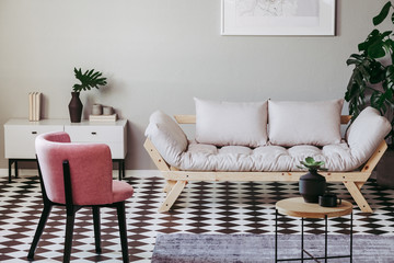 Pastel pink chair in beige and grey living room interior