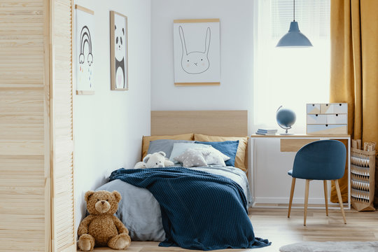 Desk, chair and single bed with blue bedding in cozy bedroom interior for children