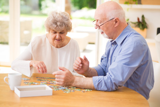 Elder couple assembling the puzzle together
