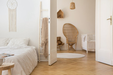 Scandinavian bedroom with white bedding on the bed and door open to stylish nursery with white wooden crib and wicker peacock chair, real photo