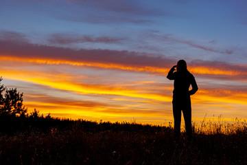 Fototapeta Kobieta patrząca w dal na tle zachodu słóńca obraz