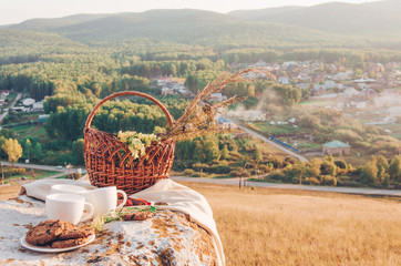 Picnic lunch with landscape background. Three coffee cups, basket with flowers