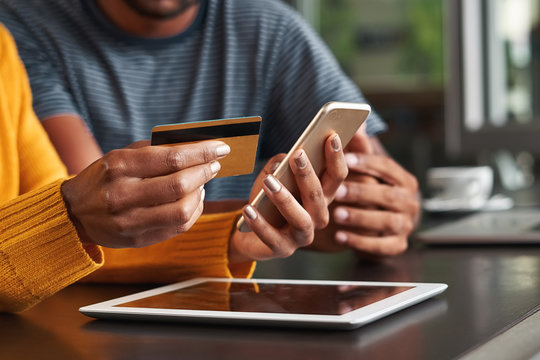 Woman in café holding credit card and mobile phone