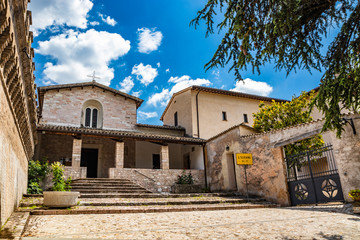 The Church of San Severino. The porch, the mullioned window, the cross, the medieval walls. In Spello, province of Perugia, Umbria, Italy.