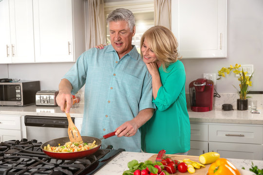 Husband and wife cooking a healthy meal with vegetables, balanced diet, health and wellness