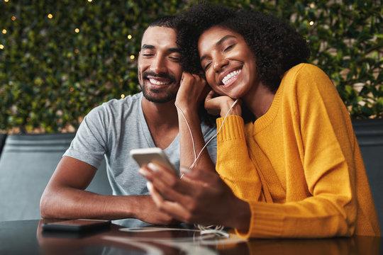 Young couple enjoying listening music on earphones