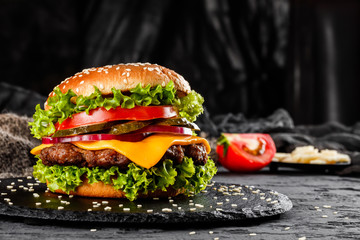 Beef burger with cheese, tomatoes, red onions, cucumber and lettuce on black slate over dark background. Unhealthy food