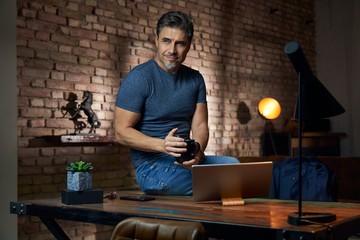 Older man working at desk using tablet