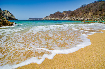 Paradise sand beach with turquoise blue water in Huatulco, Oaxaca, Mexico