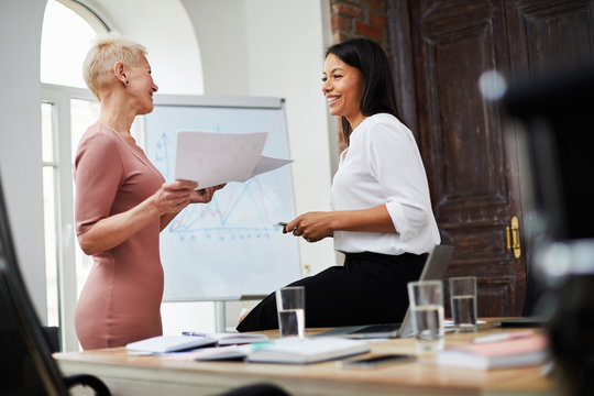 Side view portrait of two successful businesswomen chatting cheerfully while working in office, copy space