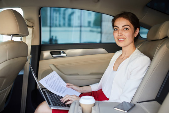 Portrait of smiling businesswoman looking at camera while working in car , copy space
