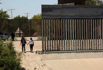 A couple hold hands after crossing illegally into the United States, in El Paso, Texas, U.S, as seen from Ciudad Juarez