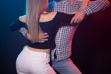 Social dance, couple, people concept - young couple dancing bachata or salsa in the night club