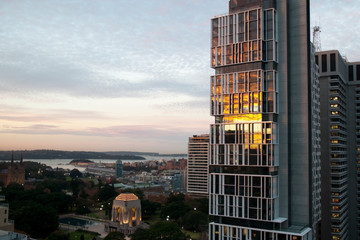 Sydney Australia, Sunset reflecting in glass of highrise apartment building with the Anzac Memorial in Hyde Park and harbour in the background
