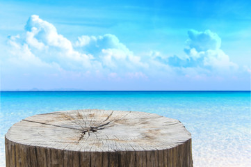 Wooden desk or stump on sand beach in summer. background. For product display Fototapete