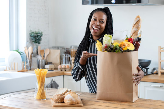Woman with grocery bag in kitchen