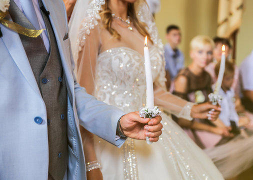 Groom in blue suit and bride in luxury dress are in church. Wedding ceremony. Couple in love holding candles.