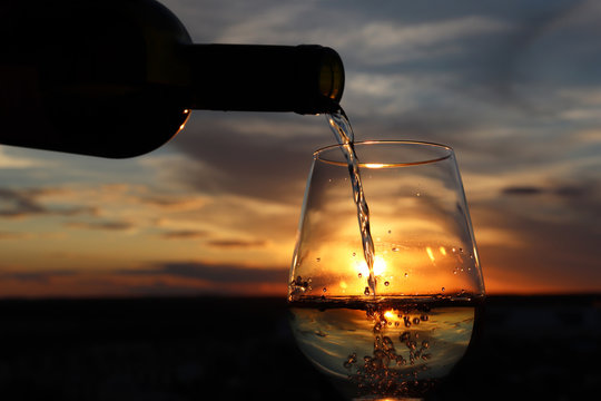 White wine pouring from a bottle into the glass on beautiful sunset background, orange sun is shining through the jet. Concept of celebration, summer party at resort, romantic dinner outdoors