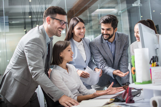 Group of happy cheerful businesspeople working around computer during meeting in modern office.