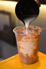 milk pour over glass of ice coffee on wooden table