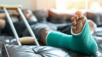Bone fracture foot and leg on male patient with splint cast and crutches during surgery rehabilitation and orthopaedic recovery staying at home