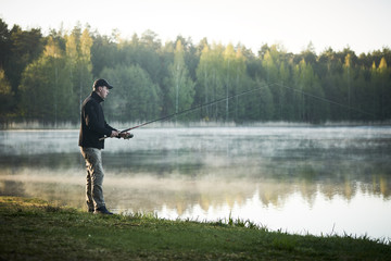 fishing. fisher with spinning rod early morning