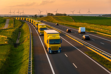 intensive highway traffic at sunset - column of trucks on the motorway in Poland