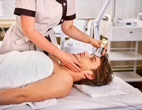 Ultrasound therapy for male skin tightening in beauty spa salon. Beautician does procedure by electric device for man in day spa .