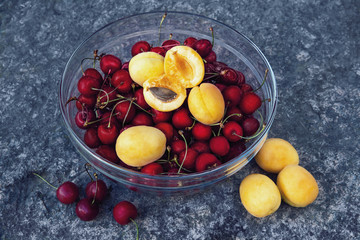 ripe yellow apricots and fresh red cherries in a glass bowl on a stone surface