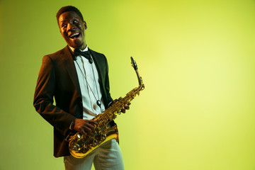 Young african-american jazz musician playing the saxophone on gradient yellow-green studio background. Concept of music, hobby, festival. Joyful attractive guy improvising. Colorful portrait of artist
