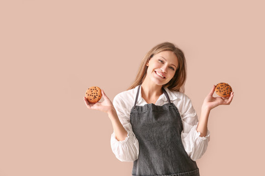 Happy female baker with tasty cookies on color background