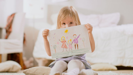 Cute Young Girl Sitting on Pillows and Shows Drawing of Her Family and Hides Behind It. Sunny Living Room.