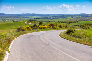 Beautiful landscape, spring nature. Winding provincial road among sunny fields in Tuscany, Italy