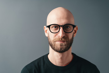 Young smiling man with beard and glasses on gray studio background
