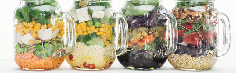 delicious vegetable salad in glass jars with handles on wooden white table isolated on white, panoramic shot