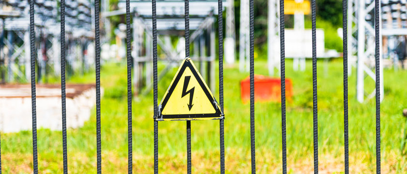Danger sign of electricity on a metal fence enclosing an electrical substation
