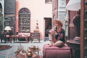 Photo sur Plexiglas Maroc Traveling by Morocco. Happy young woman in hat relaxing in traditional riad interior in medina.