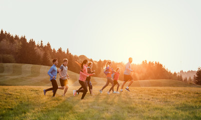 Large group of people cross country running in nature. Wall mural