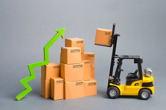 Yellow Forklift truckraises a box over a stack of boxes and a green arrow up. High trade volumes, increased production, storage infrastructure. raise economic indicators. exports, imports. sales rise