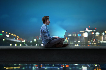 Mann sitzt am Notebook vor nächtlicher Stadt