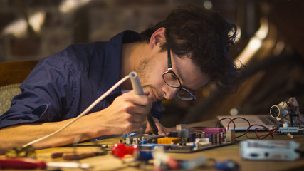 Student is studying electronics and soldering a circuit board in a garage.