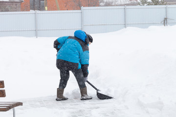 Old woman in warm blue jacket clears a snowdrifts with a snow shovel